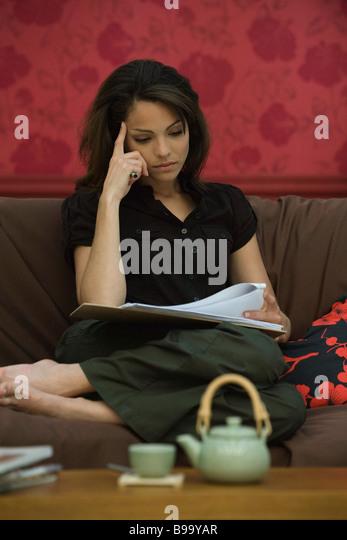 Junge Frau liest Dokument auf sofa Stockbild