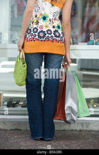 Junge Frau Schaufensterbummel, mehrere Einkaufstaschen tragen beschnitten Rückansicht Stockbild