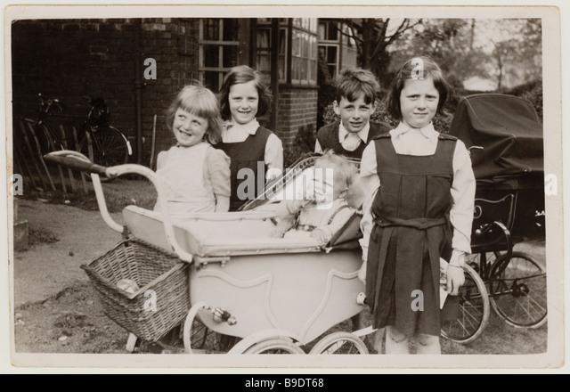 Freche junge Kinder mit Kinderwagen auf der Suche nach einem Baby außerhalb ihres Heimatlandes in den 1950er Stockbild