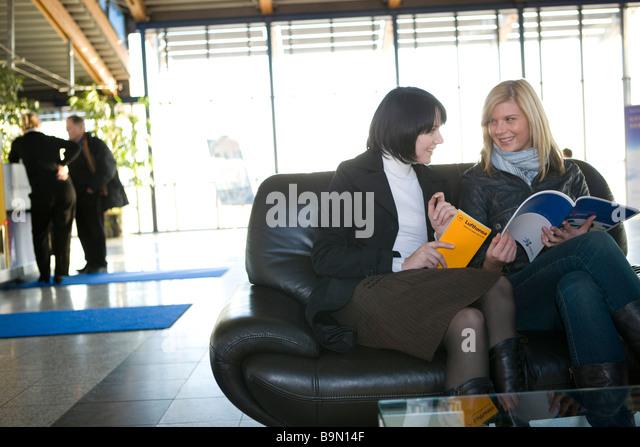 Frauen Schauen Reisekataloge eine Personen am Check-in Im Hintergund Stockbild