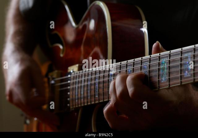 Guy Playiing electric jazz-Gitarre Stockbild