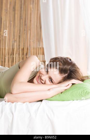 Frau lächelnd im Bett Stockbild