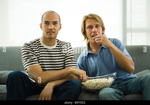 Zwei Männer sitzen auf Sofa Essen popcorn Stockbild