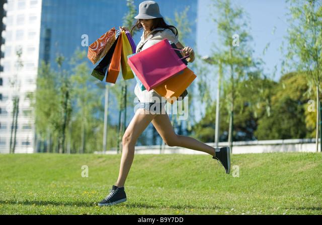Junge Frau läuft durch den Park, mehrere Einkaufstaschen tragen Stockbild