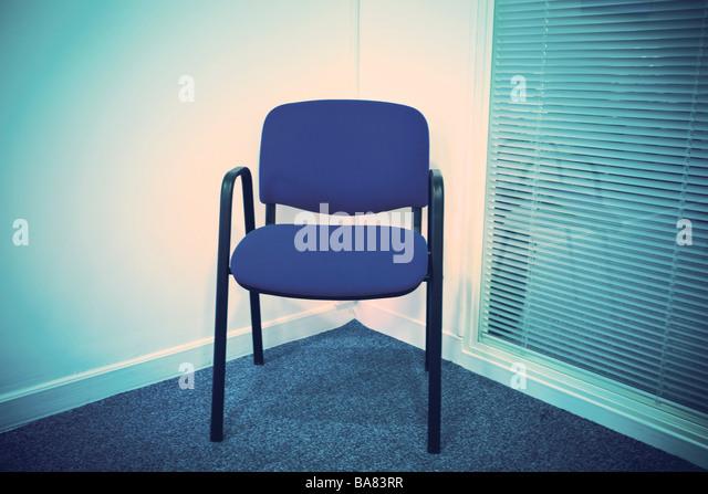 Blauer Stuhl in einer Ecke neben einer Jalousie Stockbild