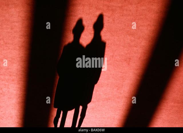 Abstrakte Sicht von einem Paar s Schatten auf einem roten Teppich Stockbild