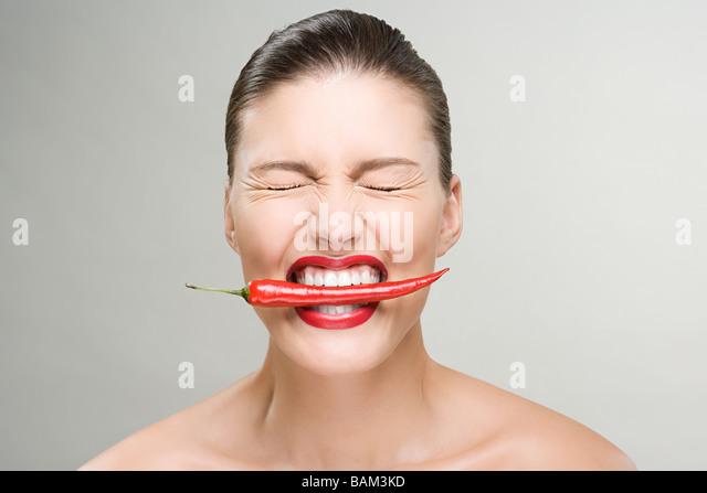 Frau mit einem roten Chili-Pfeffer in den Mund Stockbild