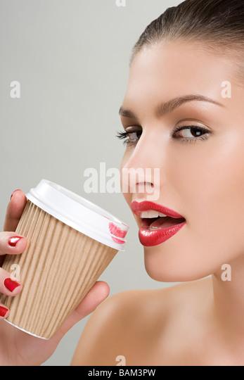 Frau trinkt Kaffee aus einem Pappbecher Stockbild