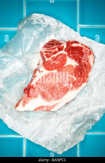 Rohes Steak auf Wachspapier auf blauer Kachel Stockbild