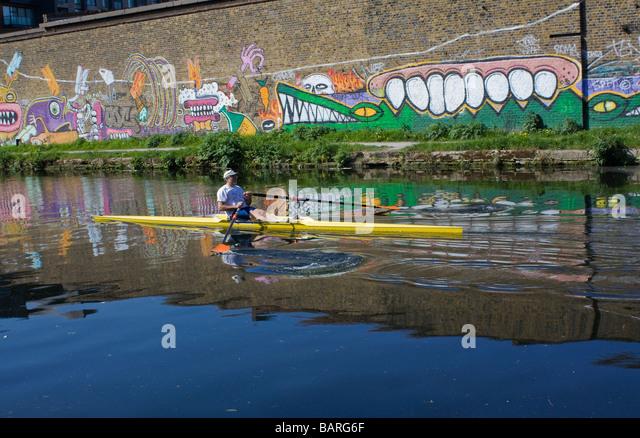Kanufahrer auf Fluss Lee London neben Wand mit Graffiti mit Krokodilen. Stockbild