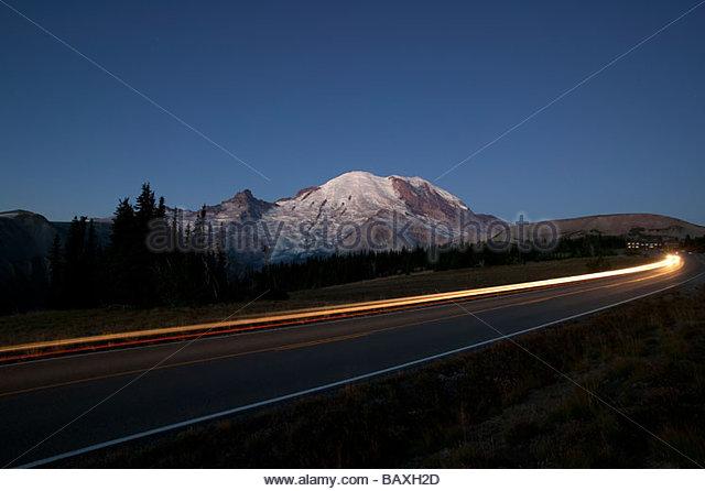 Ein Auto fährt auf der Straße nach Sonnenaufgang in Mount Rainier Nationalpark, Washington. Stockbild