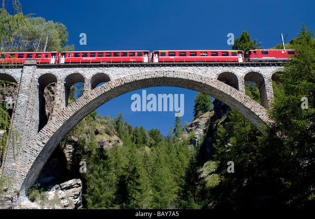 Trainieren Sie, überqueren ein Viadukt unter blauem Himmel, Guarda, Graubünden, Schweiz Stockbild