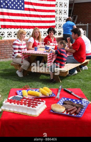 Tabelle von Lebensmitteln im Vordergrund mit Menschen Essen im Hintergrund Stockbild