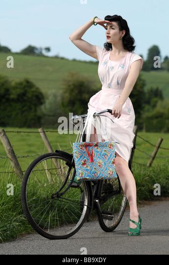 Frau trägt Vintage-Kleidung auf einem alten Fahrrad Stockbild