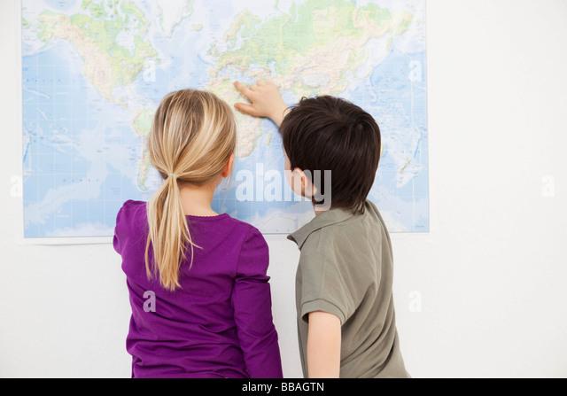 Kinder betrachten Weltkarte Stockbild
