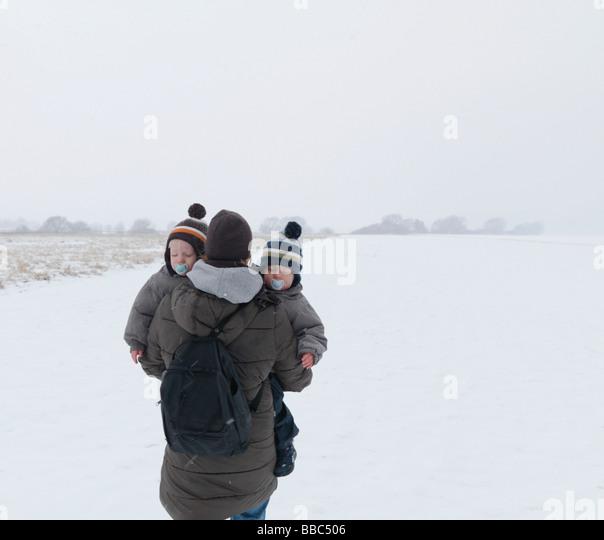 Frau zu Fuß mit Zwillingssöhne im Schnee Stockbild