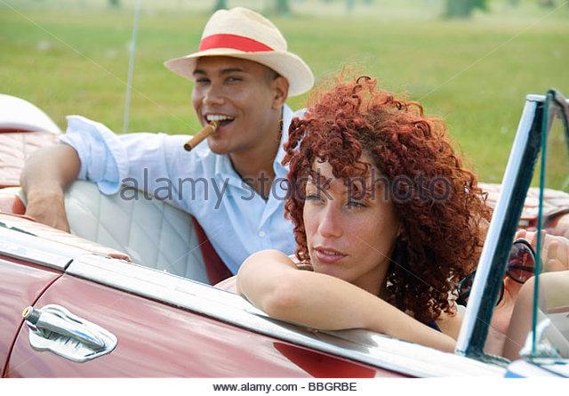 Junges Paar multi-ethnischen Auto, Mann Rauchen Hintergrund, Havanna, Kuba Stockbild