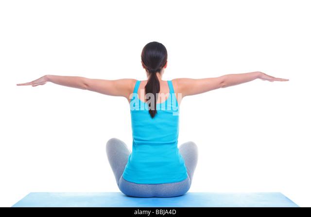 Rückansicht einer Brünette Frau setzte sich auf eine Yoga-Matte mit ihren Armen heraus in einem ausgeglichenen Stockbild