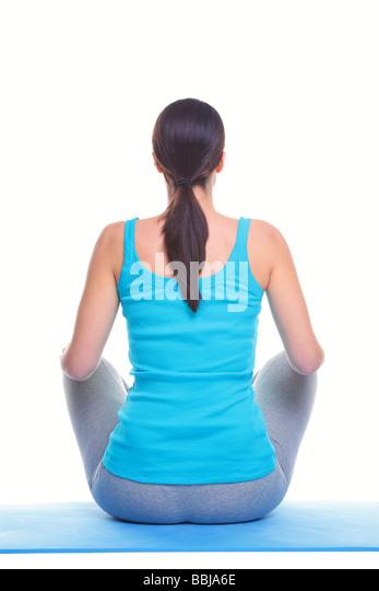 Rückansicht des eine Brünette Frau sitzt auf einer Yogamatte isoliert auf weißem Hintergrund Stockbild