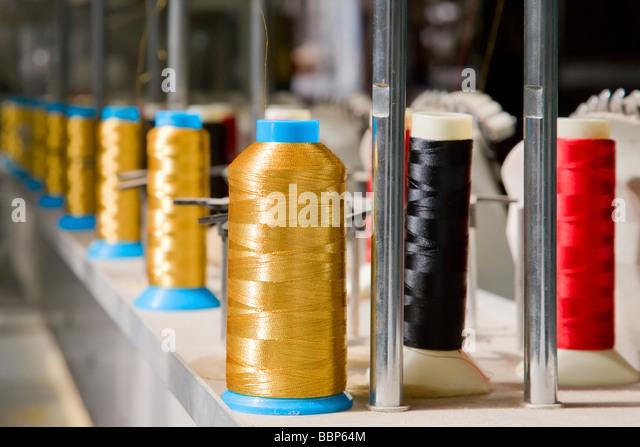 Lange Reihe von farbigen Stoff Spulen bei Herstellung Stockbild