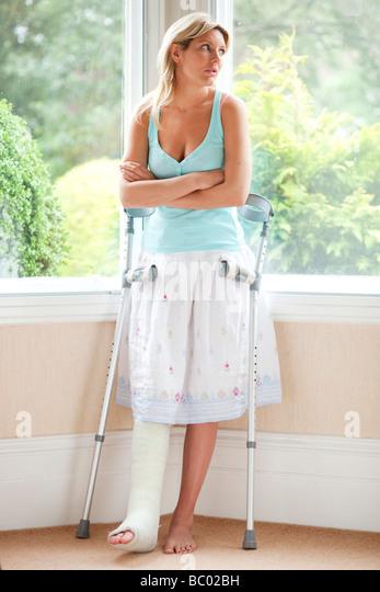 Frau zu Hause mit Gipsverband am Bein Stockbild