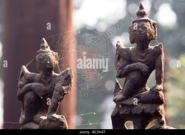 Nahaufnahme von zwei verwitterte Teakholz-Figuren in einem Kloster in Mandalay, Myanmar Stockbild