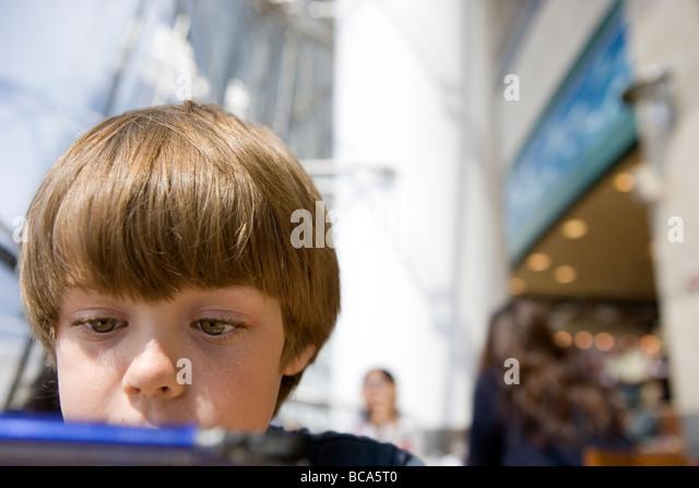 Nahaufnahme von sieben Jahre alter Junge Videospiel Nintendo ds auf einem Flughafen Stockbild