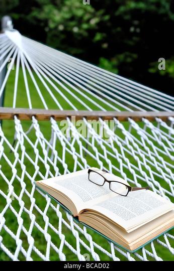 Sommer Lesung Staycation Heimat Urlaub Ruhestand Wochenende Konzept Brille Brille Brille offenes Buch Garten Hängematte. Stockbild
