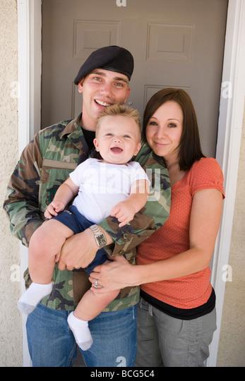 junge militärische Familien stehen vor ihrem Haus mit einjährigen Sohn. Stockbild
