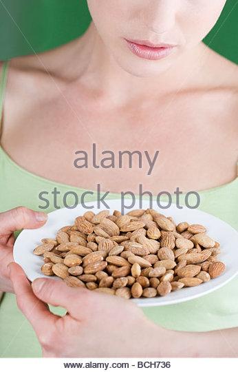 Eine junge Frau hält einen Teller mit Mandeln Stockbild