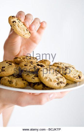 Eine Frau hält einen Teller mit Keksen, Nahaufnahme Stockbild