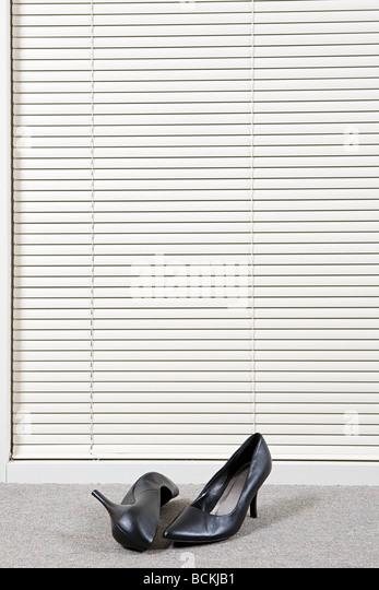 Paar hochhackigen Schuhen vor Venetian blinds Stockbild