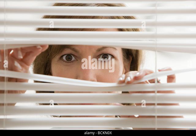 Geschäftsfrau sucht durch Jalousien Stockbild