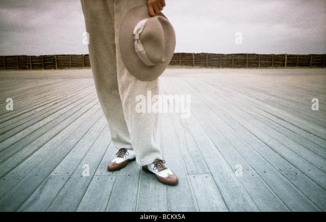 Person steht auf Holzbohlen, halten Hut Stockbild