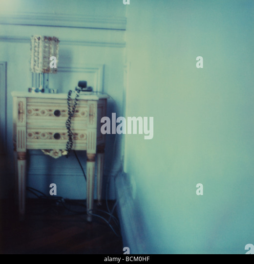 Nachttisch mit Lampe und Telefon Stockbild