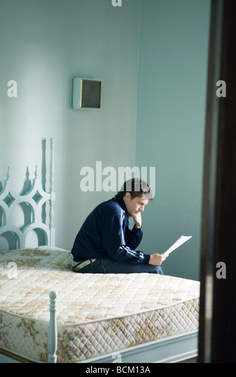 Junger Mann sitzt auf der Bettkante, Dokument lesen Stockbild