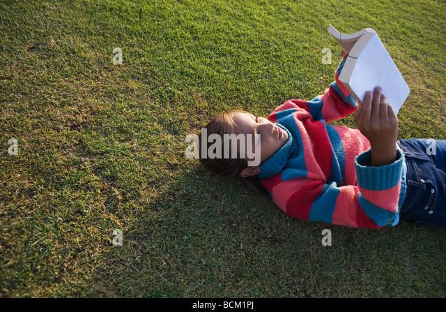 Mädchen auf Rasen Lesebuch, erhöhte Ansicht liegend Stockbild