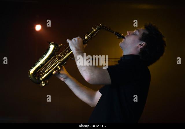 Junger Mann Saxophon im Nachtclub, Seitenansicht Stockbild