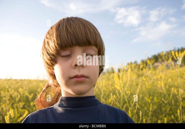 sieben Jahre alter Junge singen seine Augen schließen und hören die Vögel in einem Feld von Wildblumen, Stockbild