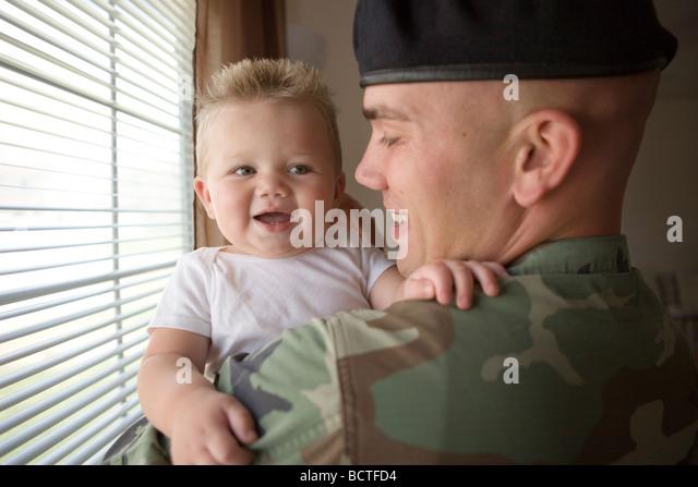 amerikanischen Militärs Vater nach Hause zu kommen und seinen kleinen Sohn mit einer Umarmung begrüßt Stockbild