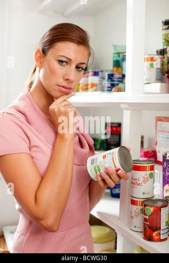 Frau betrachten Lebensmittel-Etikett auf Rückseite Zinn Stockbild