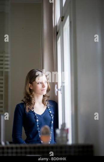 glückliches Mädchen am Fenster stehend Stockbild