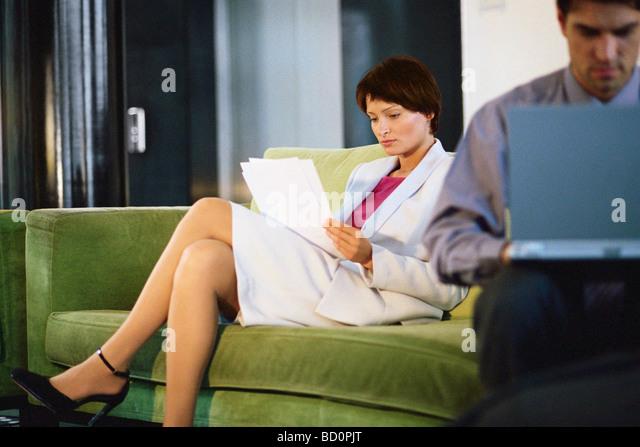 Weibliche Führungskraft Lesen von Dokumenten auf Sofa, Mann arbeitet am Laptop im Vordergrund Stockbild