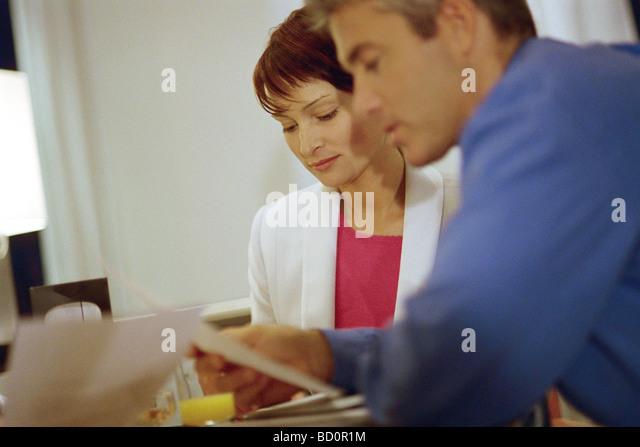 Mann und Frau sitzen am Tisch Lesen von Dokumenten Stockbild