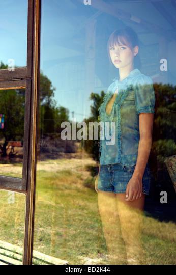 Teenager-Mädchen im Fenster stehen Stockbild