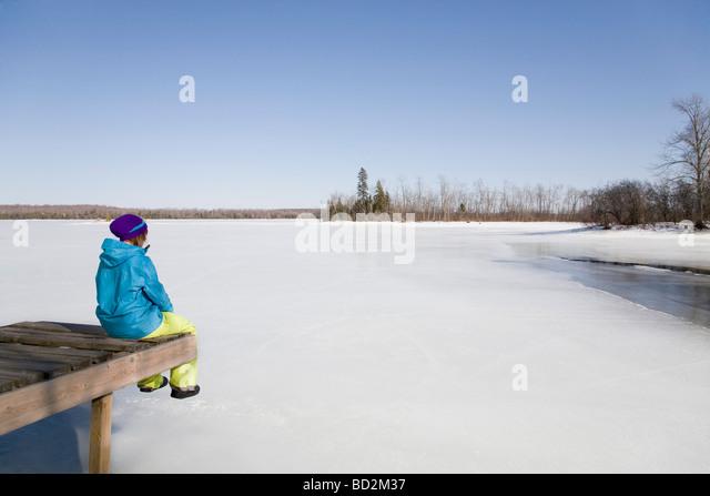 Frau entspannend am Dock von gefrorenen See Stockbild
