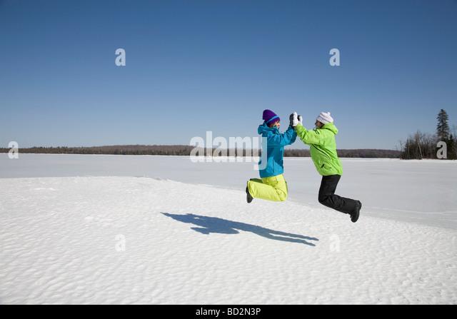 Zwei Frauen auf zugefrorenen See springen Stockbild