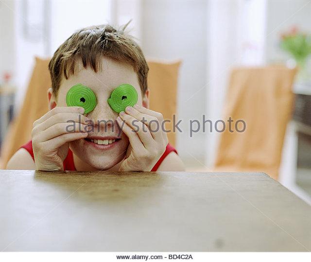 Junge grüne gewickelten Gelee-Süßwaren vor seinen Augen halten Stockbild