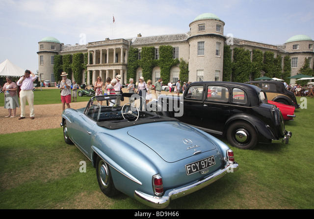 Motor-Enthusiasten betrachten Sie klassische Oldtimer parkte vor Goodwood House, West Sussex, England, UK Stockbild