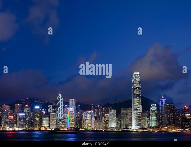 Blick über den Victoria Harbour von Hochhäusern bei Nacht in Hong Kong, China. Stockbild